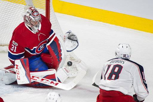 Montreal Canadiens goalie Carey Price makes a save against Columbus Blue Jackets' Pierre-Luc Dubois during the third period of an NHL hockey game in Montreal, Monday, Nov. 27, 2017. (Graham Hughes/The Canadian Press via AP)