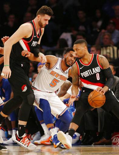 New York Knicks guard Courtney Lee (5) tries to push his way through Portland Trail Blazers center Jusuf Nurkic (27) and Trail Blazers guard Damian Lillard (0), who drives to the basket during the first half of an NBA basketball game in New York, Monday, Nov. 27, 2017. (AP Photo/Kathy Willens)