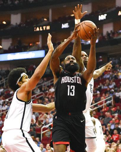 Houston Rockets guard James Harden (13) drives to the basket between Brooklyn Nets center Jarrett Allen, left, and Isaiah Whitehead during the first half of an NBA basketball game, Monday, Nov. 27, 2017, in Houston. (AP Photo/Eric Christian Smith)