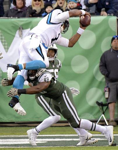 Carolina Panthers quarterback Cam Newton (1) dives over a tackle-attempt by New York Jets outside linebacker Jordan Jenkins (48) on a two-point conversion during the second half of an NFL football game, Sunday, Nov. 26, 2017, in East Rutherford, N.J. (AP Photo/Bill Kostroun)
