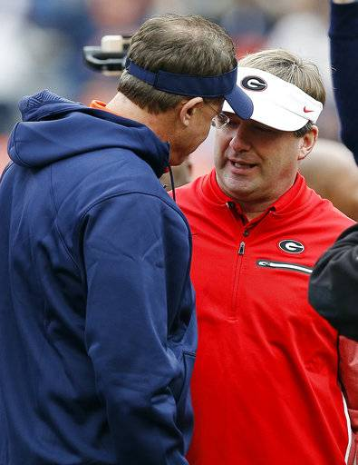 FILE - In this Nov. 11, 2017, file photo, Auburn head coach Gus Malzahn, left, and Georgia head coach Kirby Smart, right, meet before an NCAA college football game in Auburn, Ala. No. 6 Georgia is getting ready for a rematch with No. 4 Auburn in the SEC championship game. (AP Photo/Brynn Anderson, File)