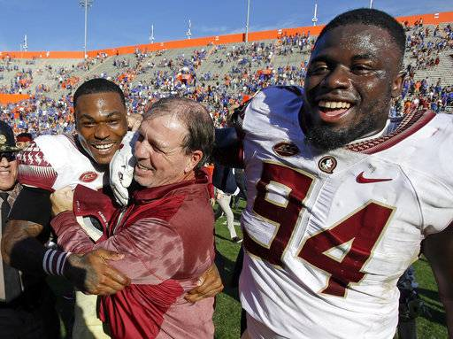 Florida State defensive back Derwin James, left, and defensive tackle Walvenski Aime (94) celebrate with Florida State head coach Jimbo Fisher, center, after defeating Florida 38-22 in an NCAA college football game, Saturday, Nov. 25, 2017, in Gainesville, Fla. Florida State won 38-22. (AP Photo/John Raoux)