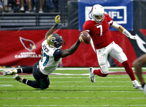 Arizona Cardinals quarterback Blaine Gabbert (7) is dragged down by Jacksonville Jaguars defensive tackle Malik Jackson (97) during the first half of an NFL football game, Sunday, Nov. 26, 2017, in Glendale, Ariz. (AP Photo/Ross D. Franklin)
