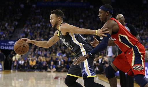 Golden State Warriors guard Stephen Curry, left, drives the ball away from New Orleans Pelicans guard Rajon Rondo during the second half of an NBA basketball game Saturday, Nov. 25, 2017, in Oakland, Calif. The Warriors won, 110-95. (AP Photo/Ben Margot)