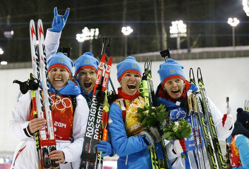 FILE - In this file photo dated Friday, Feb. 21, 2014, Russia's relay team from left, Yana Romanova, Olga Zaitseva, Ekaterina Shumilova and Olga Vilukhina, celebrate winning the silver for the women's biathlon 4x6k relay at the 2014 Winter Olympics, in Krasnaya Polyana, Russia. Yana Romanova and Olga Vilukhina have tested positive for doping at the 2014 Sochi Winter Olympics, their silver medals are forfeit and according to an IOC statement issued Monday Nov. 27, 2017, they are among five Russian athletes now banned from all future Olympics. (AP Photo/Kirsty Wigglesworth, FILE)