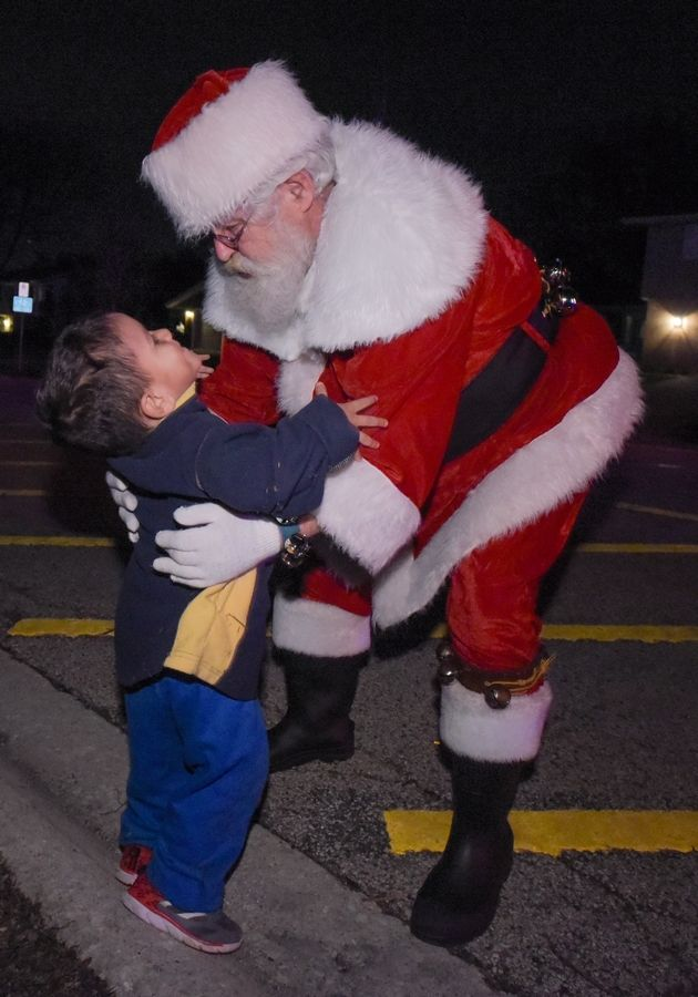 Santa gives José Aguilar, 3 of Glendale Heights a hug after arriving on a fire truck to the Bloomingdale Public Library for their annual Holiday Open House on November 28, 2017.