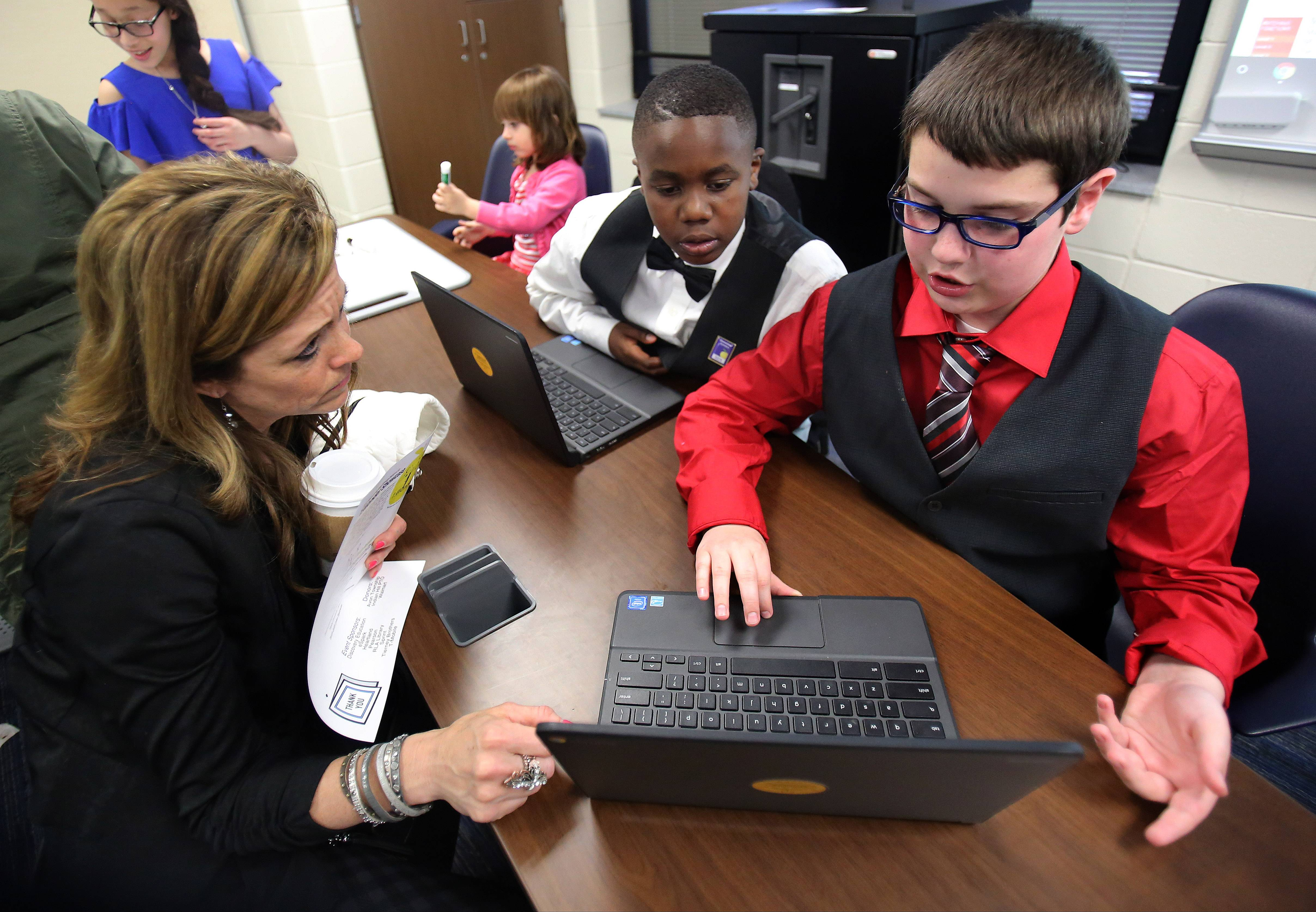 Fifth-graders from Indian Hill School in Round Lake Heights demonstrate their Google Classroom skills to Kristine Judd of Antioch during the Round Lake Area School District 116 1:Wonder Showcase l in April. The number of district students receiving laptop computers or iPads will triple next year.