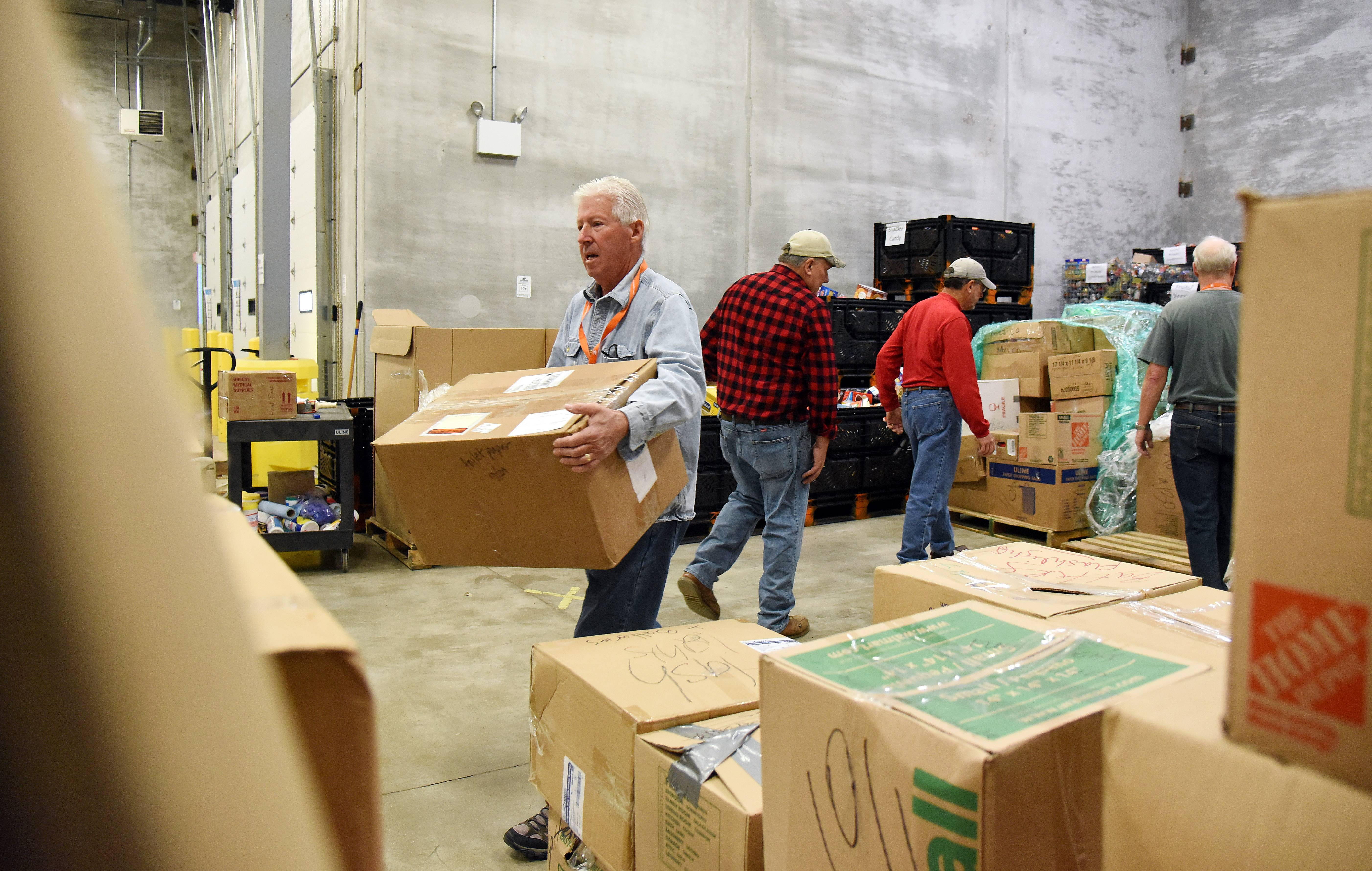 Northern Illinois Food Bank volunteer Gary Snyder of St. Charles moves boxes of donated materials to be delivered to hurricane victims in Puerto Rico.