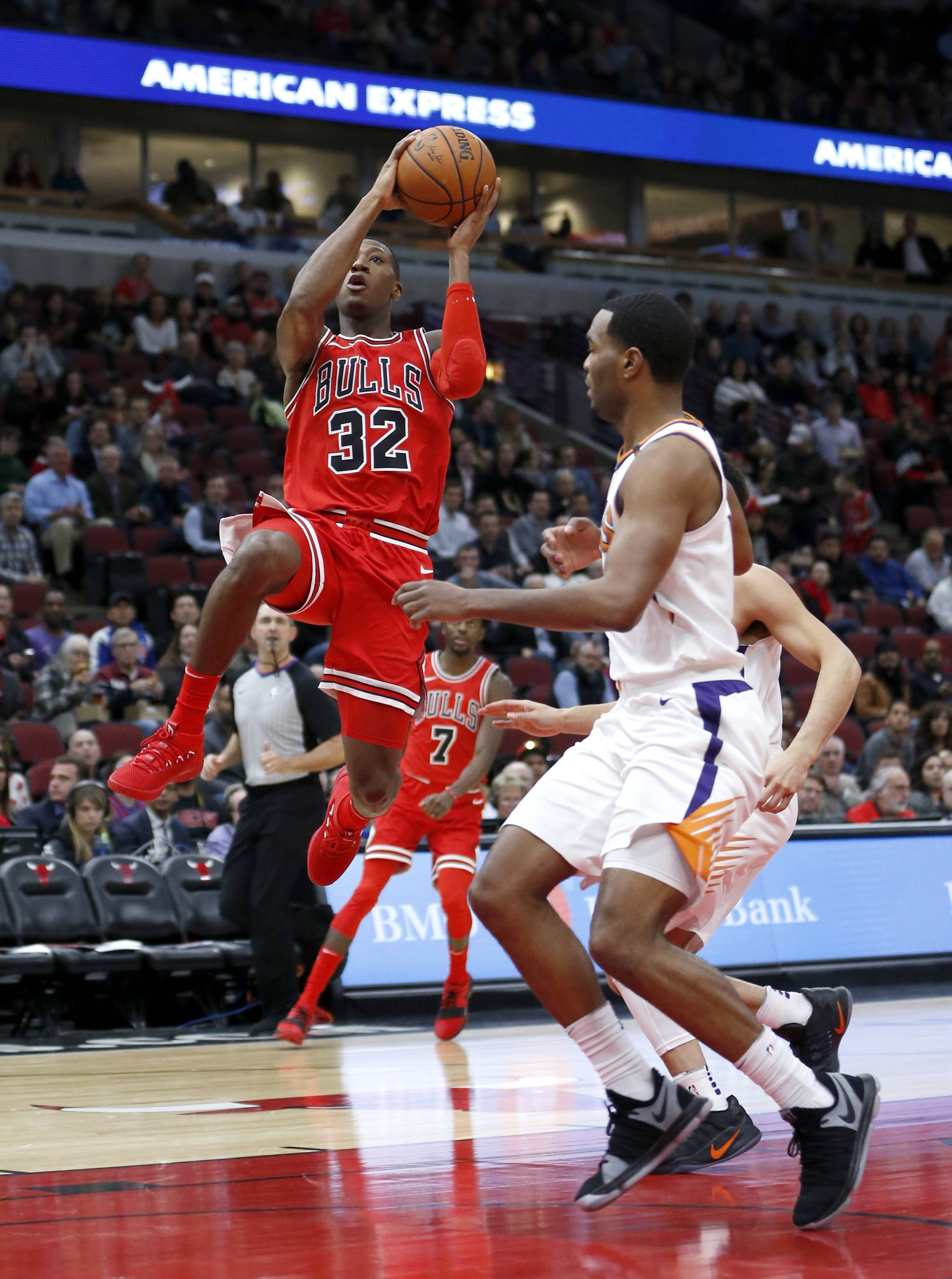 Chicago Bulls' Kris Dunn drives past Phoenix Suns' TJ Warren during the first half of an NBA basketball game Tuesday, Nov. 28, 2017, in Chicago. (AP Photo/Charles Rex Arbogast)