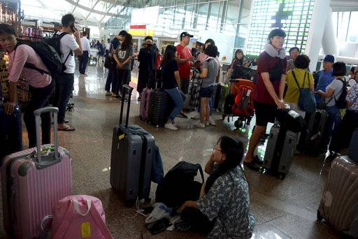 Tourists wait as Ngurah Rai International Airport is closed due to the eruption of Mount Agung in Bali, Indonesia, Wednesday, Nov. 29, 2017. The volcano with a deadly history continued to erupt on the popular resort island, stranding tens of thousands of tourists as authorities extended the closure of the airport due to concerns that jet engines could choke on the thick volcanic ash from the eruption which was moving across the island. (AP Photo/Ketut Nataan)