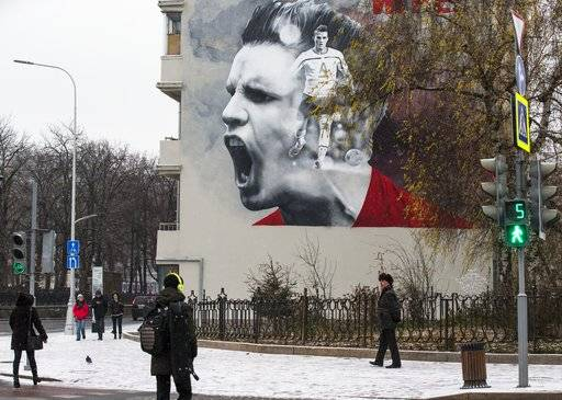 People walk past a huge poster promoting the upcoming soccer World Cup 2018 tournament in Moscow, Russia, Tuesday, Nov. 28, 2017. The World Cup will be played at 12 stadiums in 11 Russian cities. (AP Photo/Alexander Zemlianichenko)