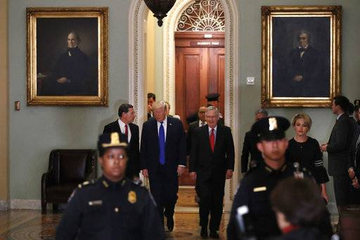 President Donald Trump, center, walks with Sen. John Barrasso, R-Wyo., left, and Senate Majority Leader Mitch McConnell of Ky., right, on Capitol Hill in Washington, Tuesday, Nov. 28, 2017. (AP Photo/Jacquelyn Martin)