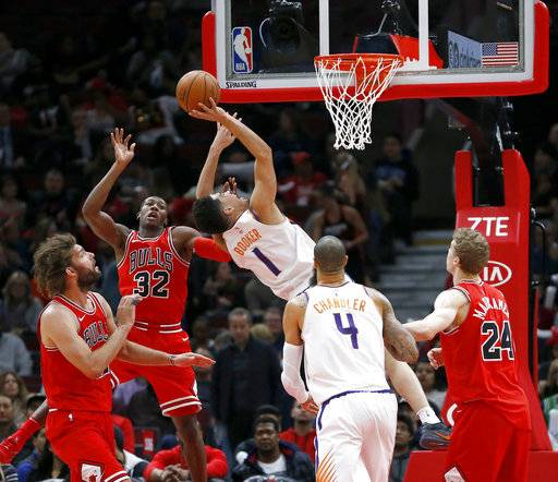 Phoenix Suns' Devin Booker (1) drives to the basket past Chicago Bulls' Kris Dunn (32) as Lauri Markkanen (24) Tyson Chandler (4) and Robin Lopez watch during the first half of an NBA basketball game Tuesday, Nov. 28, 2017, in Chicago. (AP Photo/Charles Rex Arbogast)