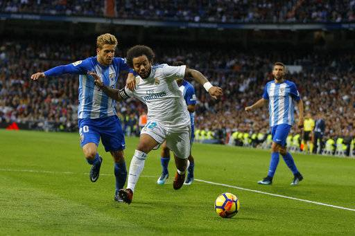 "Real Madrid's Marcelo, right, vies for the ball with Malaga's Sergio Gontan ""Keko"" during the Spanish La Liga soccer match between Real Madrid and Malaga at the Santiago Bernabeu stadium in Madrid, Saturday, Nov. 25, 2017. (AP Photo/Francisco Seco)"