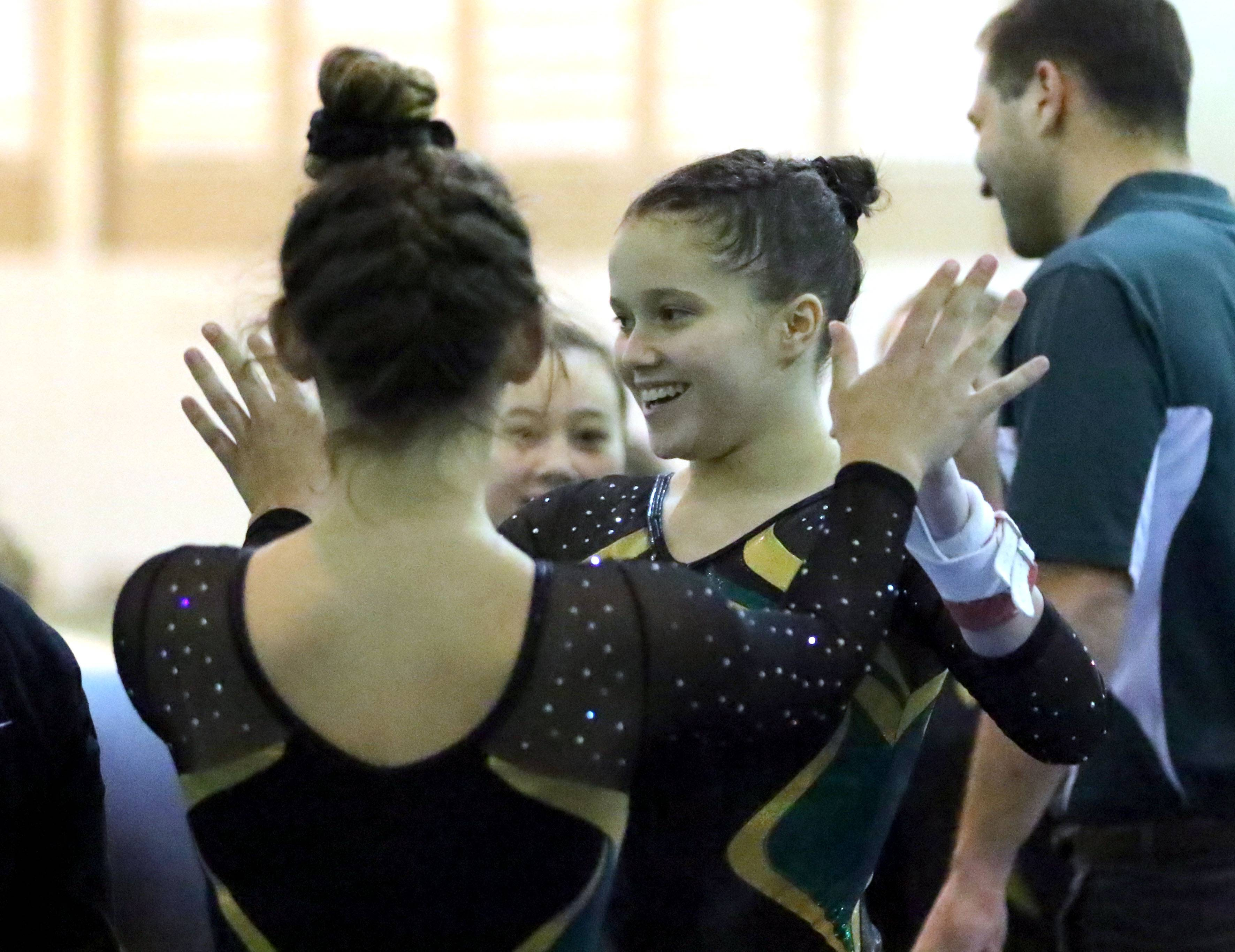 Stevenson's Emily Weinstein gets high-fives after her uneven bars routine during girls gymnastics action Wednesday at Stevenson.