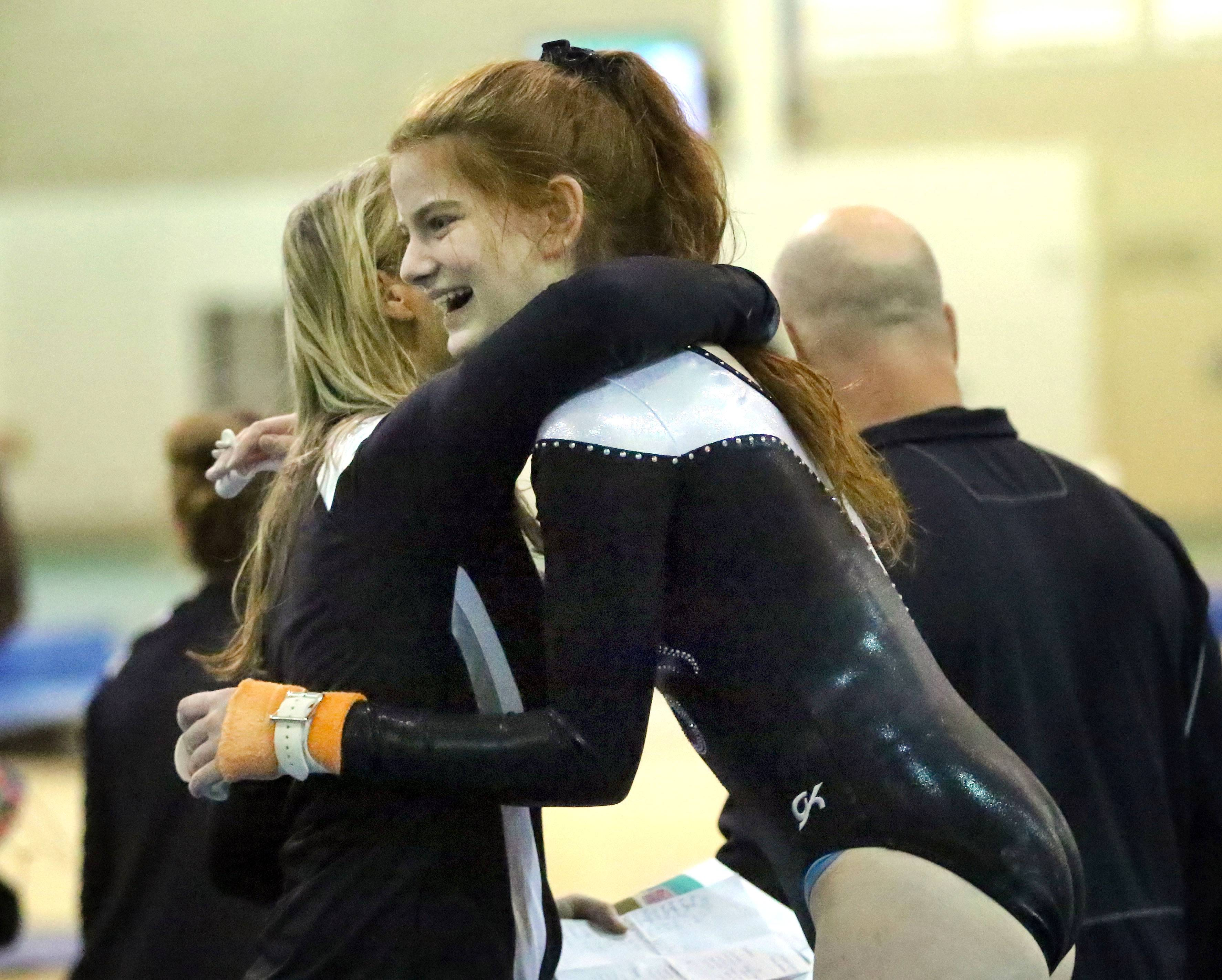 Libertyville's Constance Zanze gets a hug from coach Tiffany Owens after her bars routine Wednesday at Stevenson.
