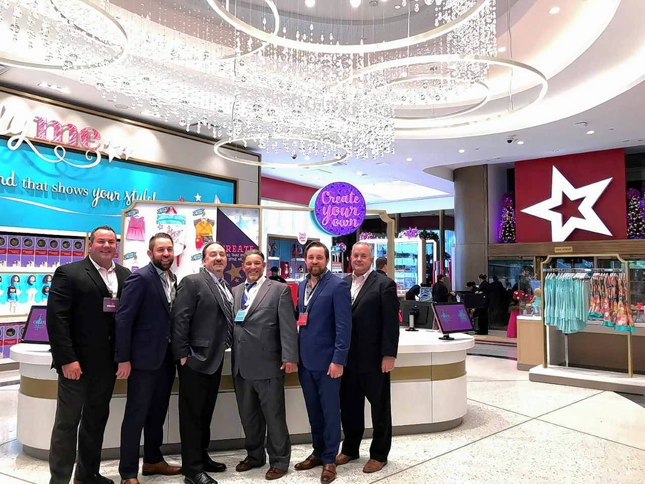 Englewood Construction completed the build-out of the new American Girl Place New York at 75 Rockefeller Plaza. Members of the Englewood team who attended the grand opening included (left to right): Chuck Taylor, director of operations; Andy Achino, project engineer, facilities division; David Arnolde, director of construction and project manager; Ira Stroud, project superintendent; Corey Achino, project manager, facilities division; and William Di Santo, president.