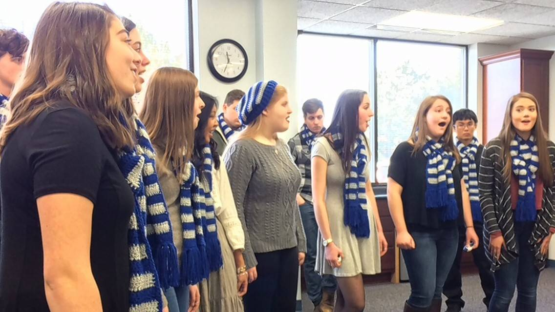 Skylar Torrey, left, and other members of the Vernon Hills High School chamber choir sing Friday for employees at the Libertyville-Vernon Hills Area High School District 128 main office.