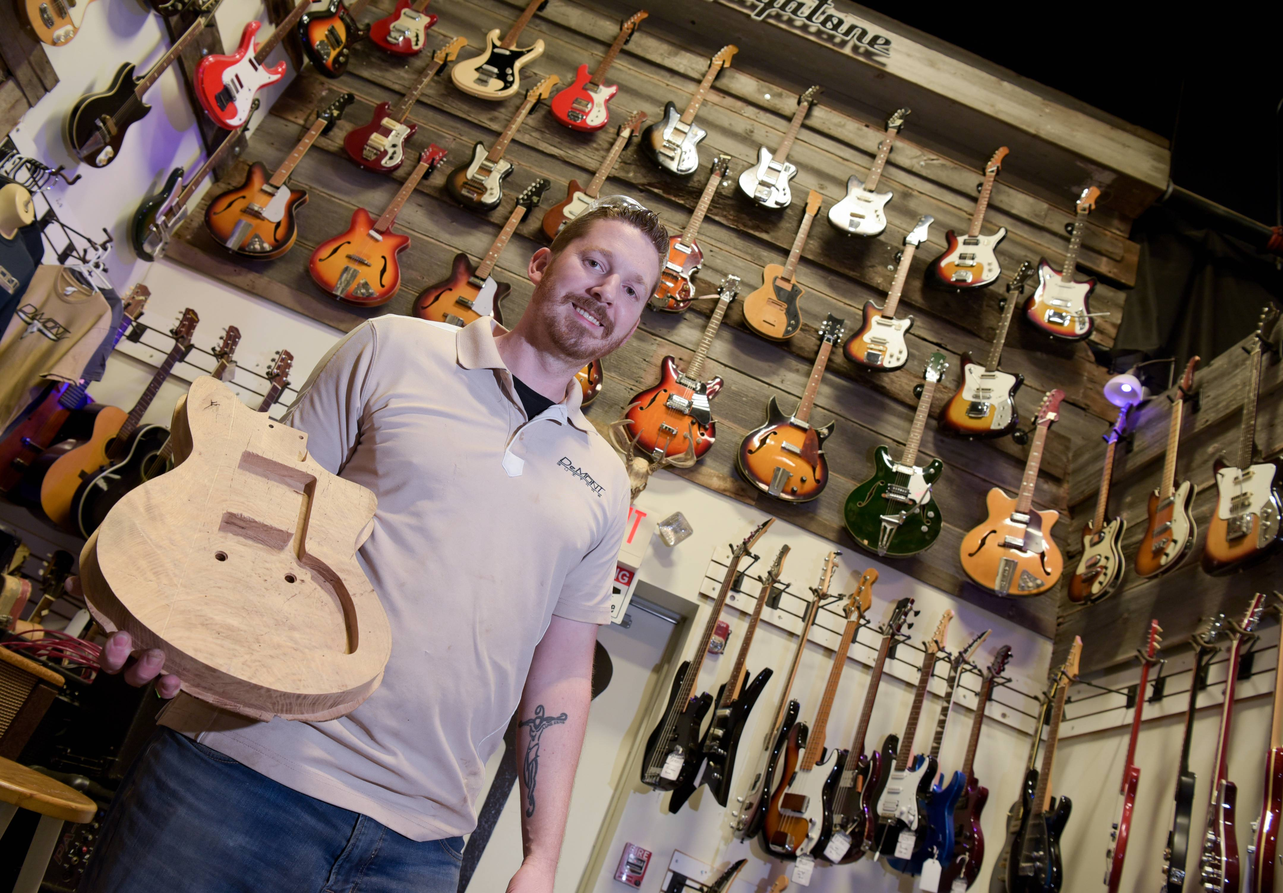 Nate DeMont of DeMont Guitars is one of at least 25 artisans turning pieces of a former tree near Naperville called the Hobson Oak into works of art that can be sold for charity.