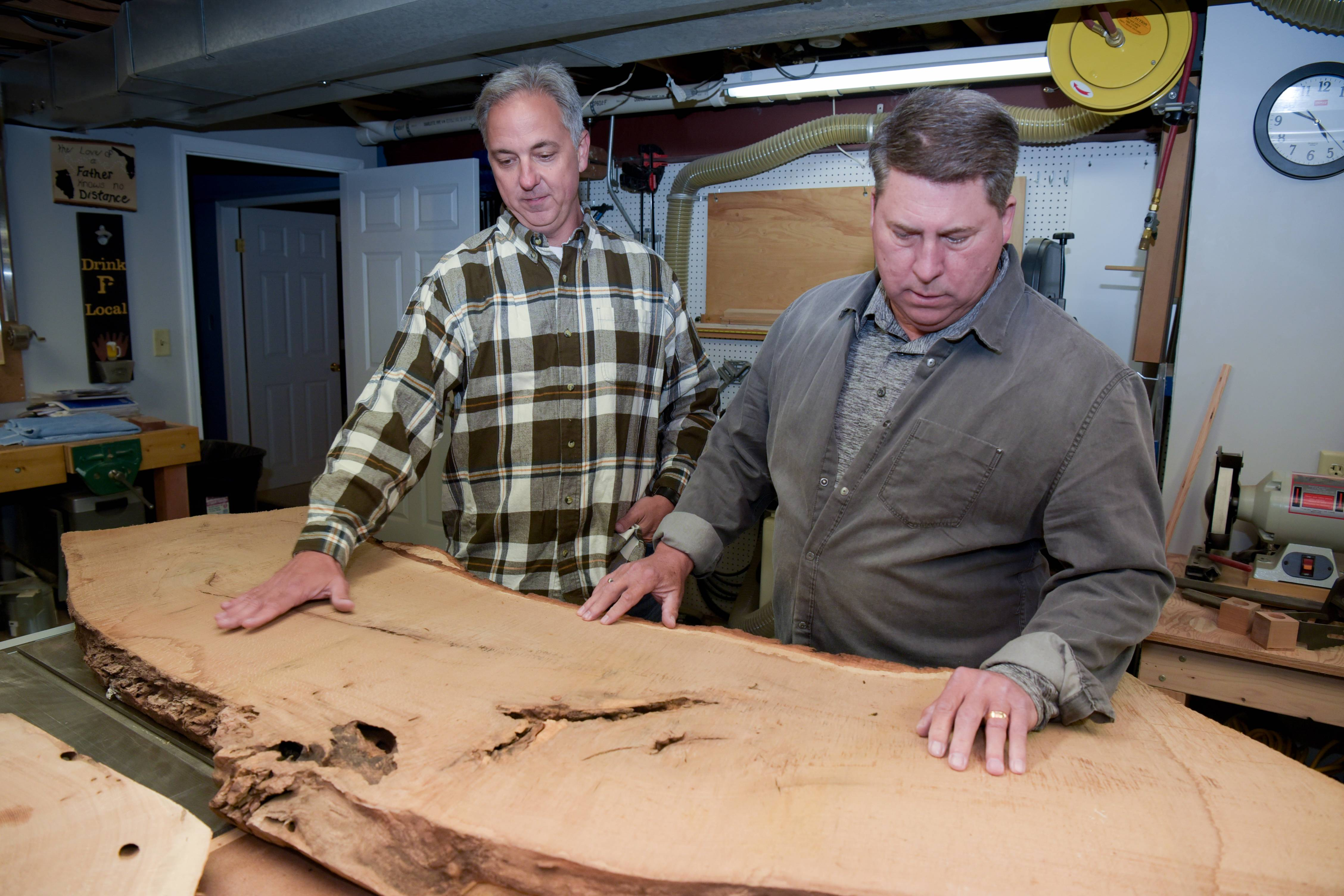 Naperville neighbors Perry Martin and Dave Horton work in Martin's basement to assess the pieces of wood they've received from the Hobson Oak.