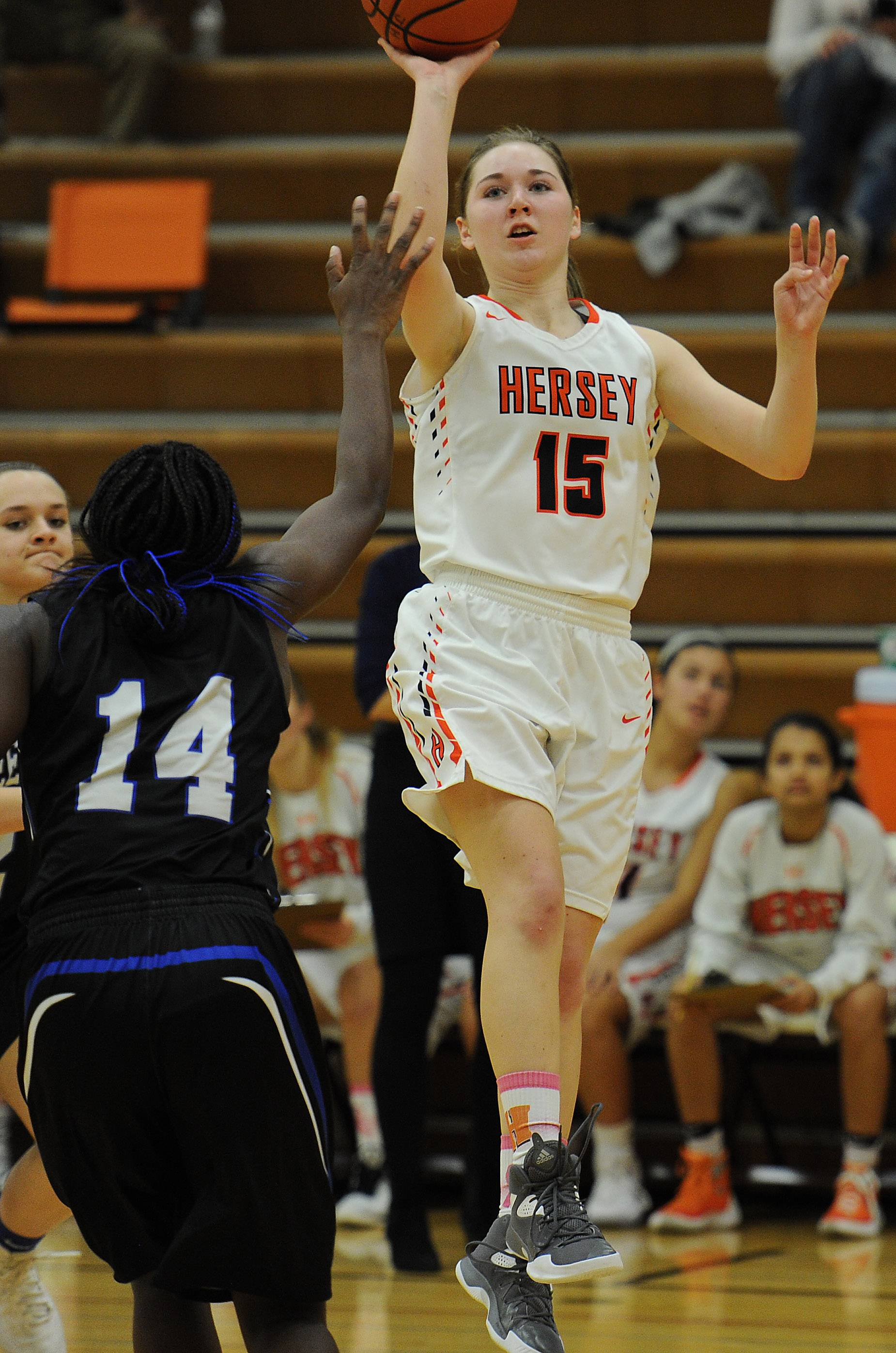 Hersey's Emily Collins delivers despite pressure from Wheeling's Nosa Igiehon in the second half of Hersey's 45-31 victory over visiting Wheeling.