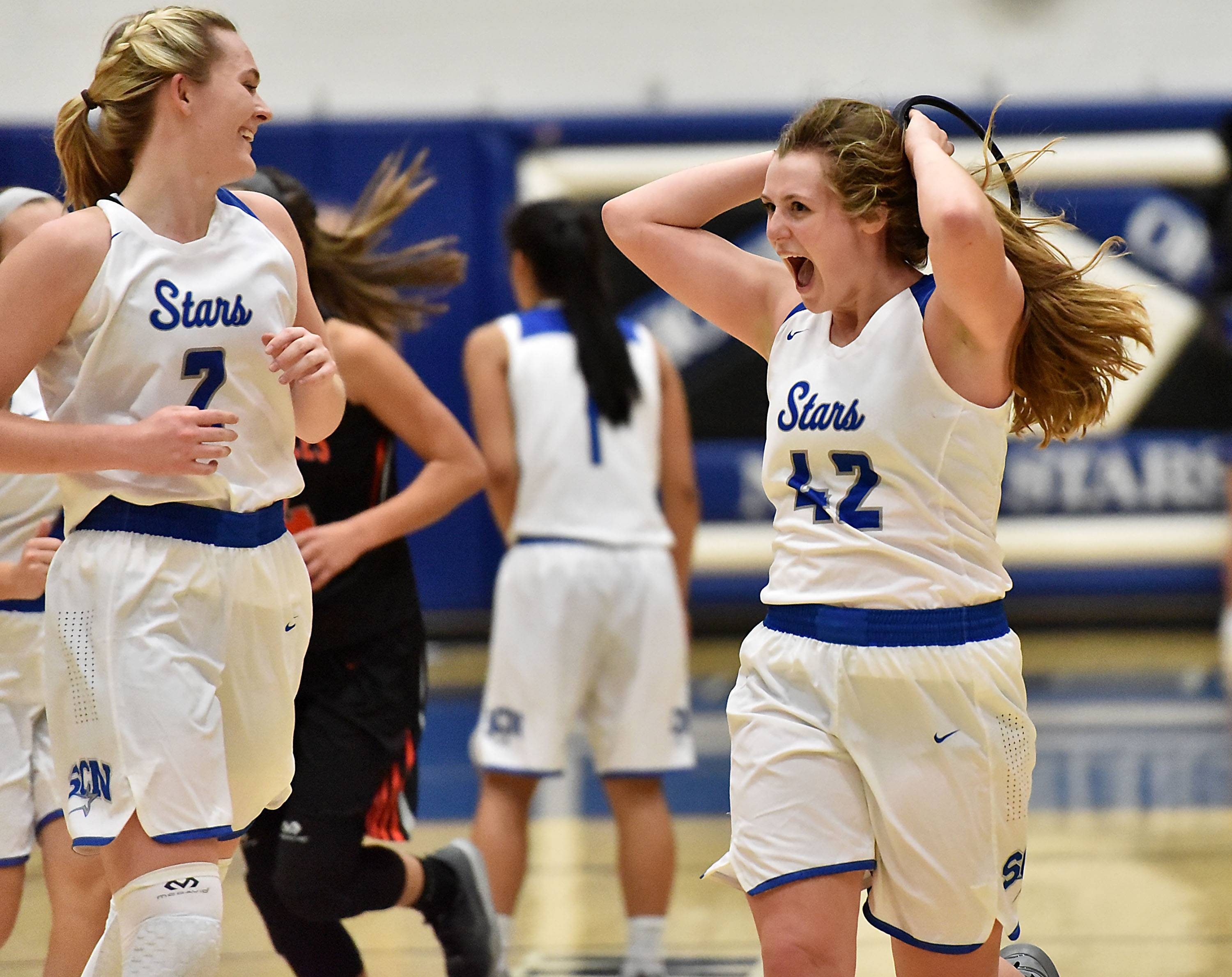 St. Charles North's Anna Tate, right, and Anna Davern celebrate their comeback win over St. Charles East Friday.