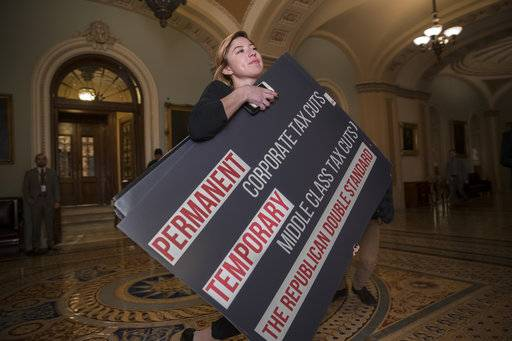 An aide for Sen. Ron Wyden, D-Ore., carries a poster that he used on the Senate floor to criticize the Republican tax bill, on Capitol Hill in Washington, Friday, Dec. 1, 2017. (AP Photo/J. Scott Applewhite)