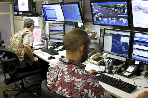 Hawaii Emergency Management Agency officials work at the department's command center in Honolulu on Friday, Dec. 1, 2017. A siren blared across Hawaii on Friday for the first time since the end of the Cold War in an effort to prepare tourists and residents for a possible nuclear attack from North Korea. The state is the first to bring back the Cold War-era warning system, Hawaii emergency management officials said. The wailing siren sounded for a minute after the usual testing of the steady alert for tsunamis and other natural disasters that Hawaii residents are used to hearing. (AP Photo/Caleb Jones)