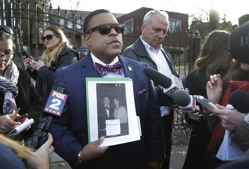 Standing outside Michigan Rep. John Conyers' house, attorney Arnold Reed addresses the media, Friday, Dec. 1, 2017, in Detroit. Reed is holding a photo of the congressman and Marion Brown, one of at least three women who have alleged sexual harassment while working for Conyers. Reed said that the congressman will discuss whether to resign following allegations of sexual misconduct in the coming days, but his health will be the paramount factor and not pressure from Washington politicians. (AP Photo/Carlos Osorio)