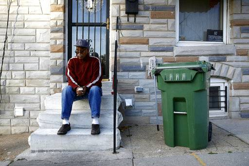 "In this Nov. 27, 2017 photo, Harold Perry sits on a stoop in front of his home, across the street from the site of Freddie Gray's arrest, in the Sandtown-Winchester neighborhood of Baltimore. These days, it's hard to find anyone in this neighborhood of generational poverty and disenfranchisement who admits to believing that police involved Gray's arrest might somehow be held responsible. ""There was never going to be any justice,"" Perry said bitterly. ""Maybe someone had hopes once upon a time, but justice is a very hard thing to come by around here."" (AP Photo/Patrick Semansky)"