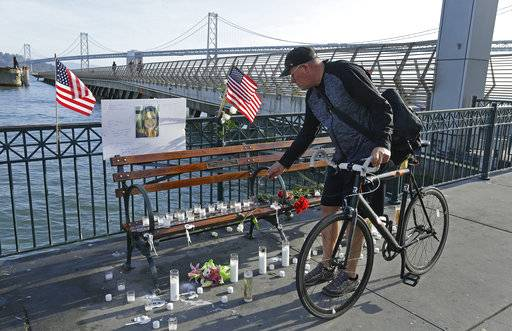 Craig Warner of Palo Alto, Calif., leaves a bell at a memorial site for Kate Steinle on Pier 14 Friday, Dec. 1, 2017, in San Francisco. In this fiercely liberal city, city leaders remained attached to San Francisco's sanctuary city status despite a not guilty verdict in a killing that sparked feverish immigration debates because the man who fired the gun was in the country illegally after being deported five times. (AP Photo/Ben Margot)