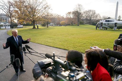 President Donald Trump speaks to members of the media before boarding Marine One at the White House, Saturday, Dec. 2, 2017, in Washington. Trump is traveling to New York for a fundraising event. (AP Photo/Andrew Harnik)
