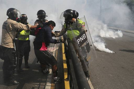 "FILE - In this May 20, 2017 file photo, Venezuelan state security forces detain a protester amid tear gas during a demonstration by opponents of President Nicolas Maduro blocking a major highway in Caracas, Venezuela. According to Human Rights Watch on Wednesday, Nov. 29, 2017, state security forces systematically abused opposition protesters detained during months of deadly political unrest earlier this year, in what the rights group described as a level of repression ""unseen in Venezuela in recent memory.�"