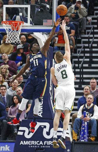 Utah Jazz forward Jonas Jerebko (8) shoots as New Orleans Pelicans guard Jrue Holiday (11) defends in the first half during an NBA basketball game Friday, Dec. 1, 2017, in Salt Lake City. (AP Photo/Rick Bowmer)