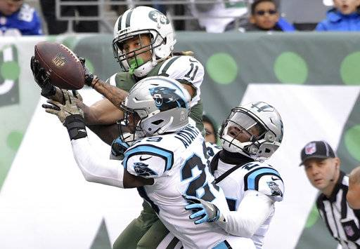 FILE- In this Sunday, Nov. 26, 2017, New York Jets wide receiver Robby Anderson, top, goes up to make a touchdown catch as Carolina Panthers strong safety Mike Adams (29) and cornerback James Bradberry (24) defend during the first half of an NFL football game in East Rutherford, N.J. Anderson is becoming one of the most exciting players in the NFL with touchdown receptions in five straight games for the Jets. (AP Photo/Bill Kostroun, File)