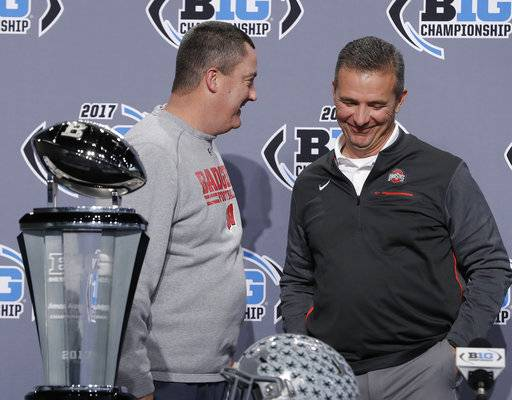 Wisconsin head coach Paul Chryst, left, talks with Ohio State head coach Urban Meyer during a news conference for the Big Ten Conference championship NCAA college football game, Friday, Dec. 1, 2017, in Indianapolis. Wisconsin will play Ohio State on Saturday for the championship. (AP Photo/Darron Cummings)