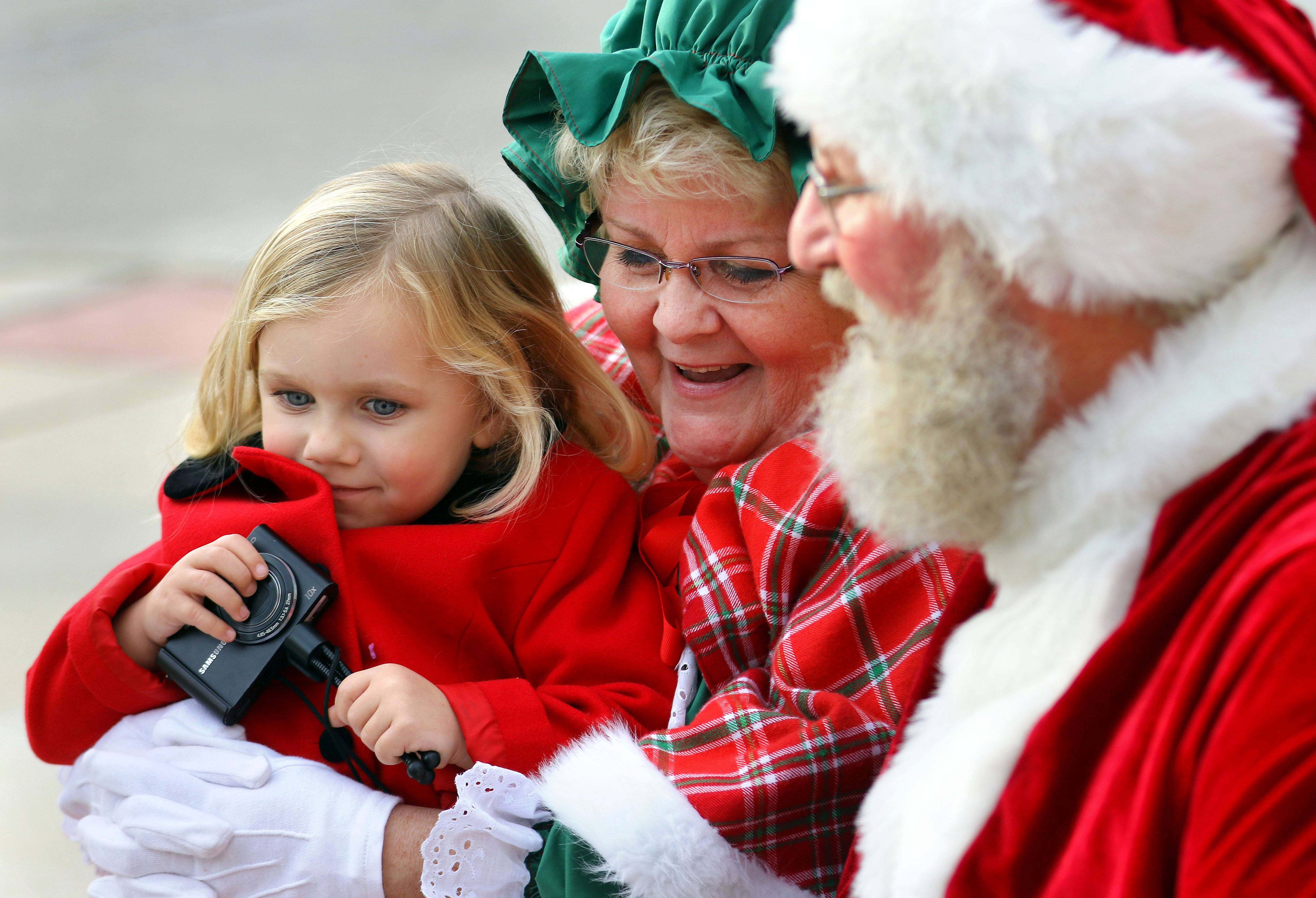 Four-year-old Lilly Ciejka sits with Santa and Mrs. Claus as Wauconda held its annual Holiday Walk on Main Street Saturday afternoon.
