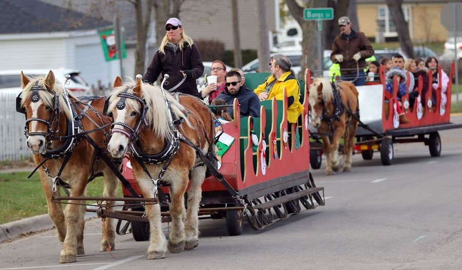 People enjoy a horse-drawn sleigh ride during Wauconda's annual Holiday Walk in downtown Wauconda Saturday afternoon.