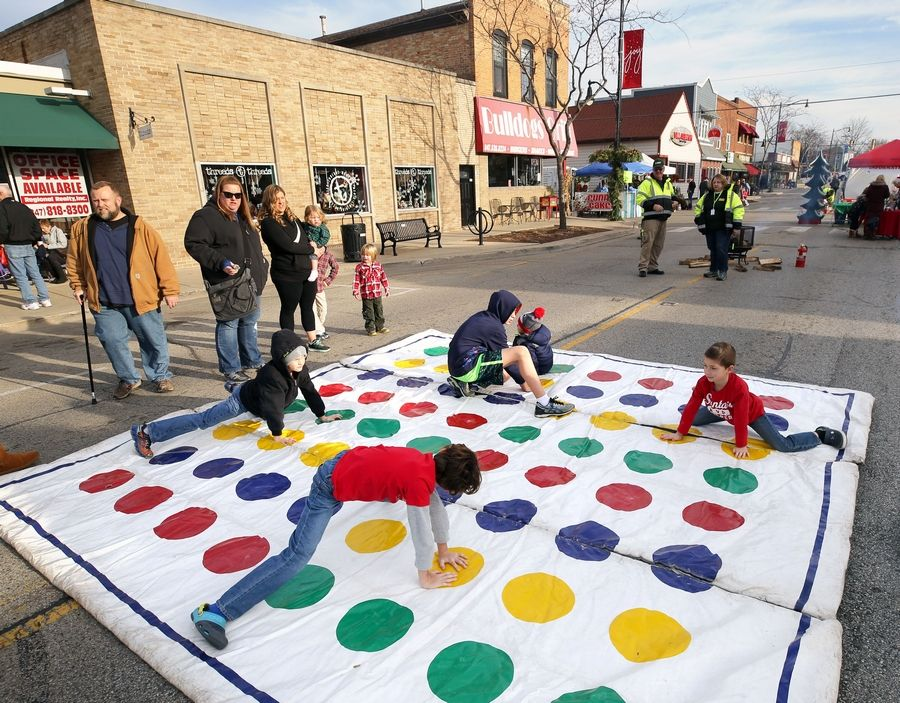 Kids play Twister in the middle of Main Street at Wauconda's Holiday Walk Saturday afternoon.