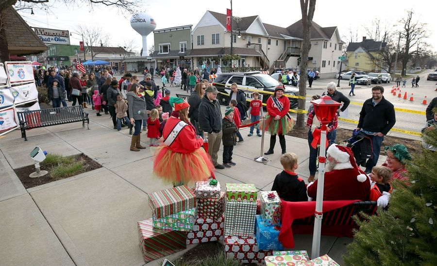 Steve Lundy/slundy@dailyherald.comPeople line up to see Santa during Wauconda's annual Holiday Walk on Main Street Saturday afternoon.