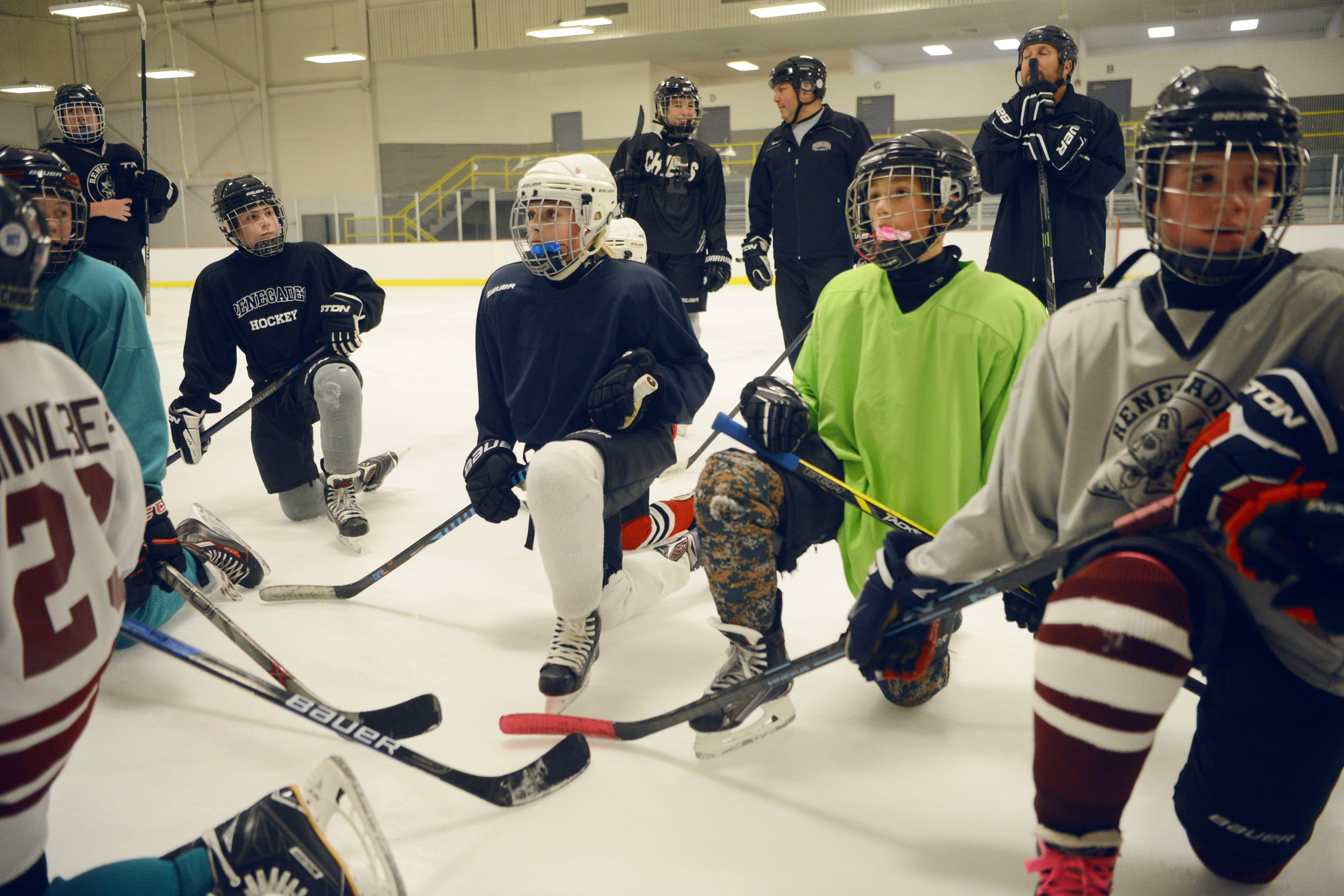 Eli Ternovits, 12, (white helmet) and her teammates pause as their coach goes over a drill at a recent practice. Eli is one of a growing legion of young female hockey players across the country.