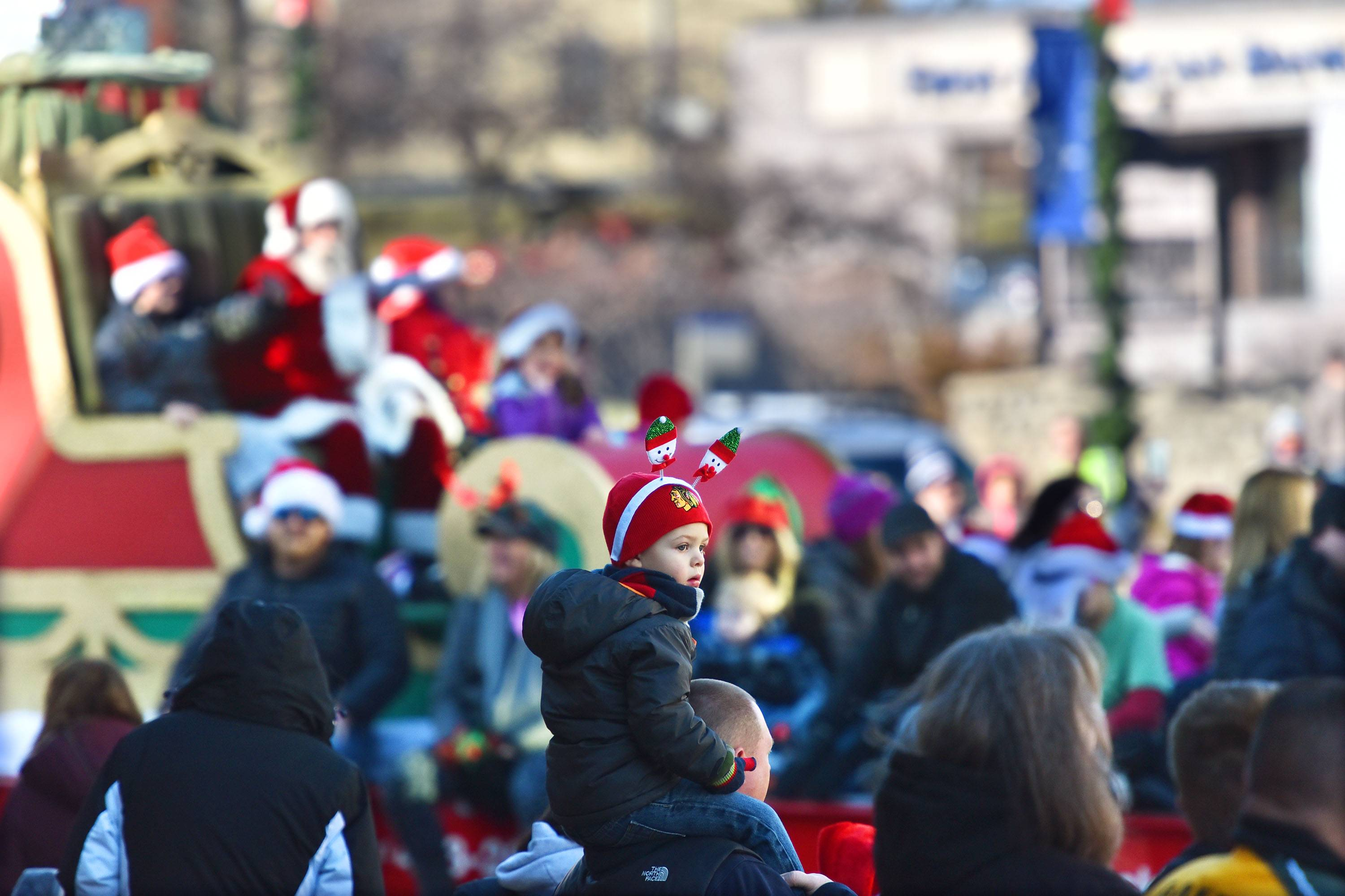 Trevor Crumpley, 3, doesn't notice that Santa Claus is coming down Main Street during the Dickens in Dundee Christmas Parade that started in West Dundee and crossed the Fox River to East Dundee on Saturday. Trevor was wearing a holiday ornament hat while sitting on the shoulders of his dad, Bob Crumpley of Algonquin.