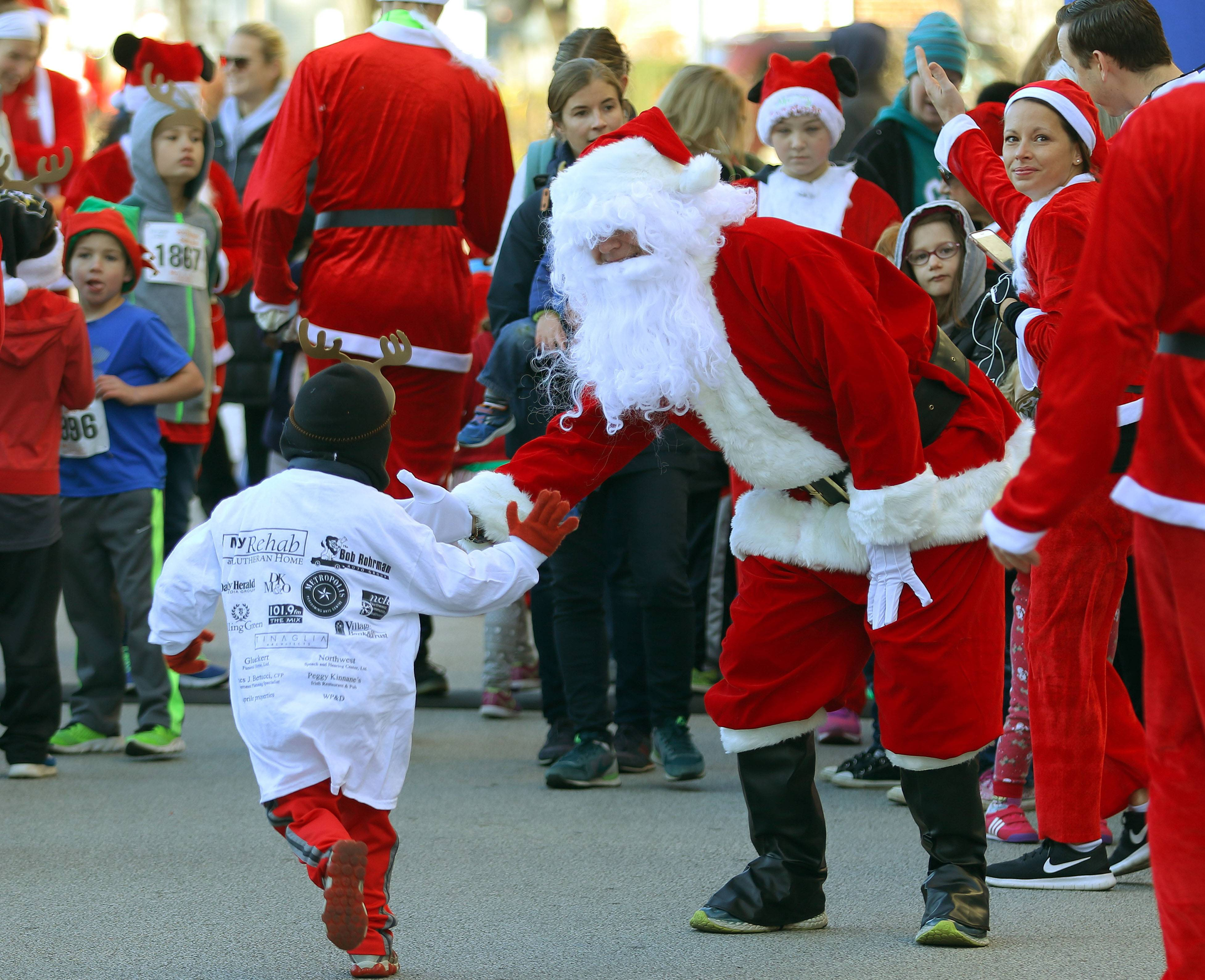 Santa high-fives kids participating in the four-block Reinder Run during the 10th annual Rotary Santa run in downtown Arlington Heights Saturday.