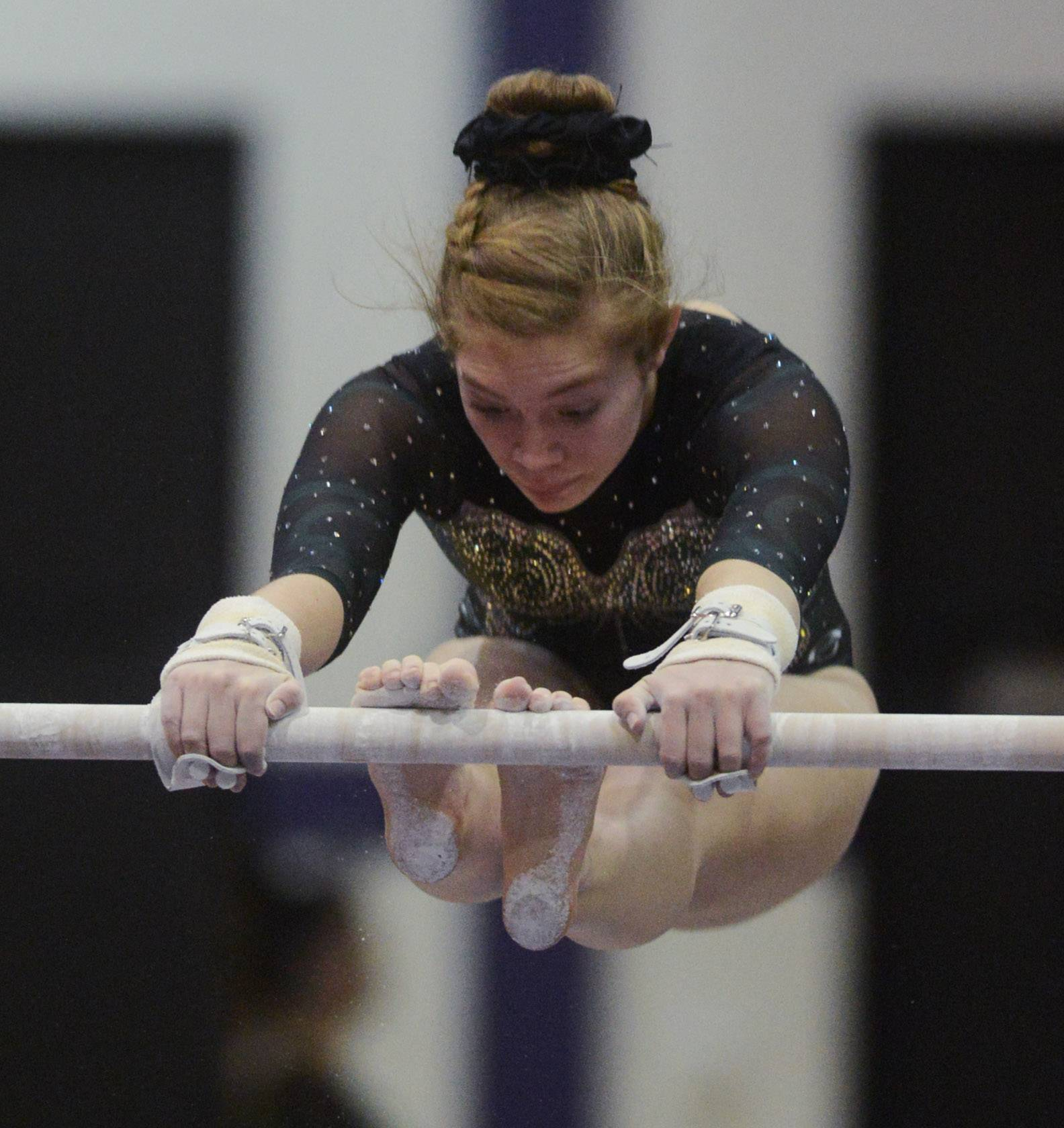 Glenbard West's Claire McGurk competes on the uneven parallel bars during the Rolling Meadows invite Saturday.