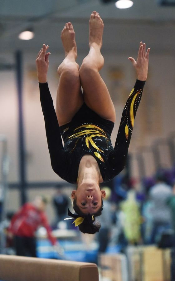 Carmel's Aideen Cazzini dismounts from the balance beam during the Rolling Meadows invite Saturday.
