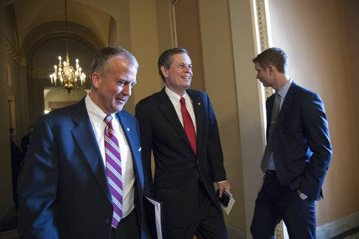 Sen. Dan Sullivan, R-Alaska, left, walks with Sen. Steve Daines, R-Mont., as they head to the Senate chamber after a closed-door meeting with Republican lawmakers to advance the GOP overhaul of the tax code, on Capitol Hill in Washington, Friday, Dec. 1, 2017. (AP Photo/J. Scott Applewhite)