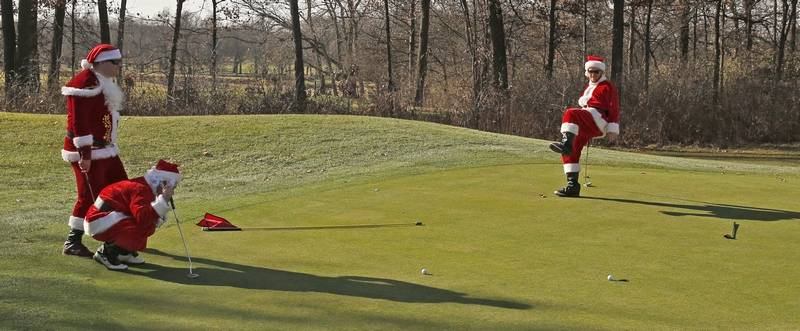 More than 100 golfers don santa suits for march of dimes quinton cook of chicago right puts some body english on his putt which spiritdancerdesigns Choice Image