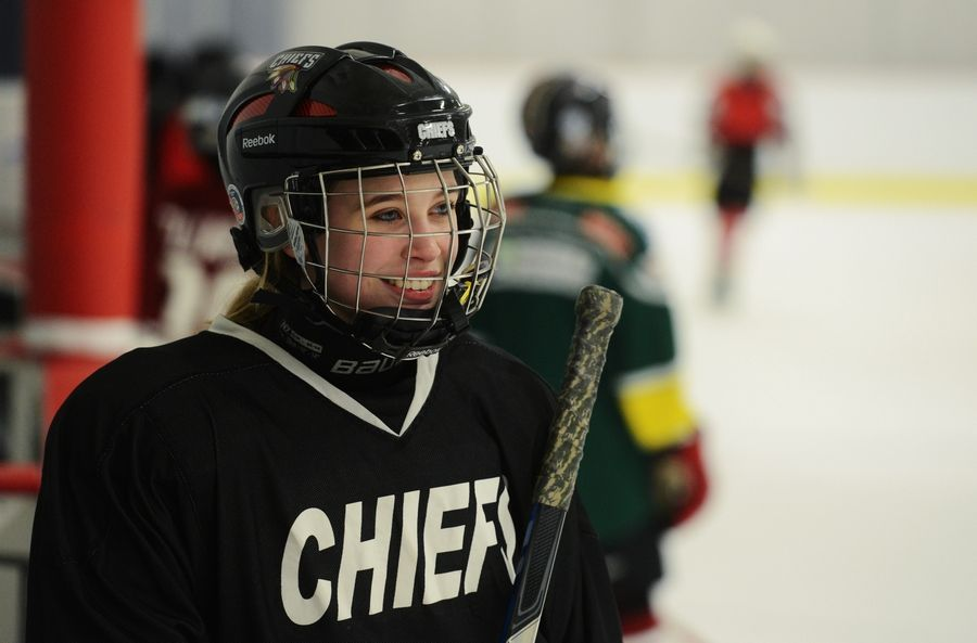 Drew Ternovits, a junior varsity player on the otherwise all boys D211 Chiefs hockey team, helps at her 12-year old sister Eli's Rolling Meadows Renegades practice.
