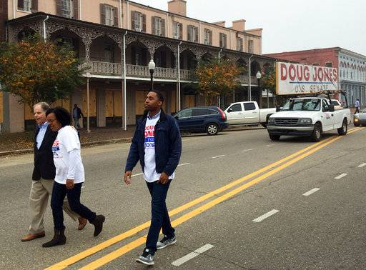 Doug Jones, left, the Democratic candidate for U.S. Senate, walks in a Christmas parade Saturday, Dec, 2, 2017, in Selma, Ala. Jones is trying to shore up support among black voters in his U.S. Senate race against Republican Roy Moore by appealing for an end to the divisiveness that has long been part of the state's politics. (AP Photo/Jeff Amy)