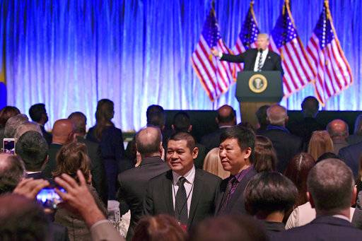 People in the audience have their photo taken as President Donald Trump speaks at a fundraiser at Cipriani in New York, Saturday, Dec. 2, 2017. Trump is attending a trio of fundraisers during his day in New York. (AP Photo/Susan Walsh)